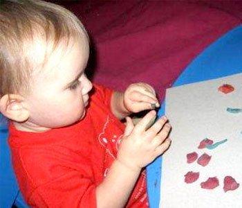 Ребенок лепит из пластилина цветы